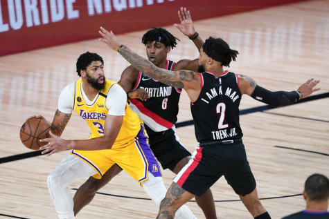 Anthony Davis (3) looks for an open Laker while being guarded by two Blazers.
