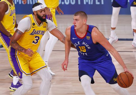Nikola Jokic (15) keeps his eyes up court while being guarded by Anthony Davis